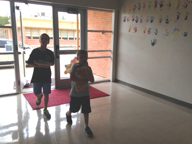 Oak Creed kids bringing books into the school.