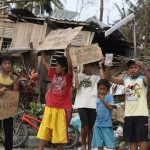 Children hold signs asking for help and food along the highway, after Typhoon Haiyan hit Tabogon town